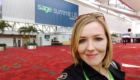 Jenn in front of Sage Summit banner